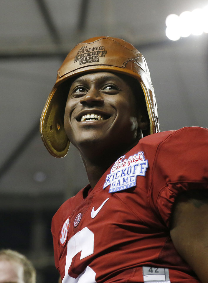 Photo - Alabama quarterback Blake Sims (6) wears a replica leather football helmet that is part of the Chick-fil-A kickoff game trophy after defeating West Virginia 33-23 in an NCAA college football game Saturday, Aug. 30, 2014, in Atlanta.  (AP Photo/Brynn Anderson)