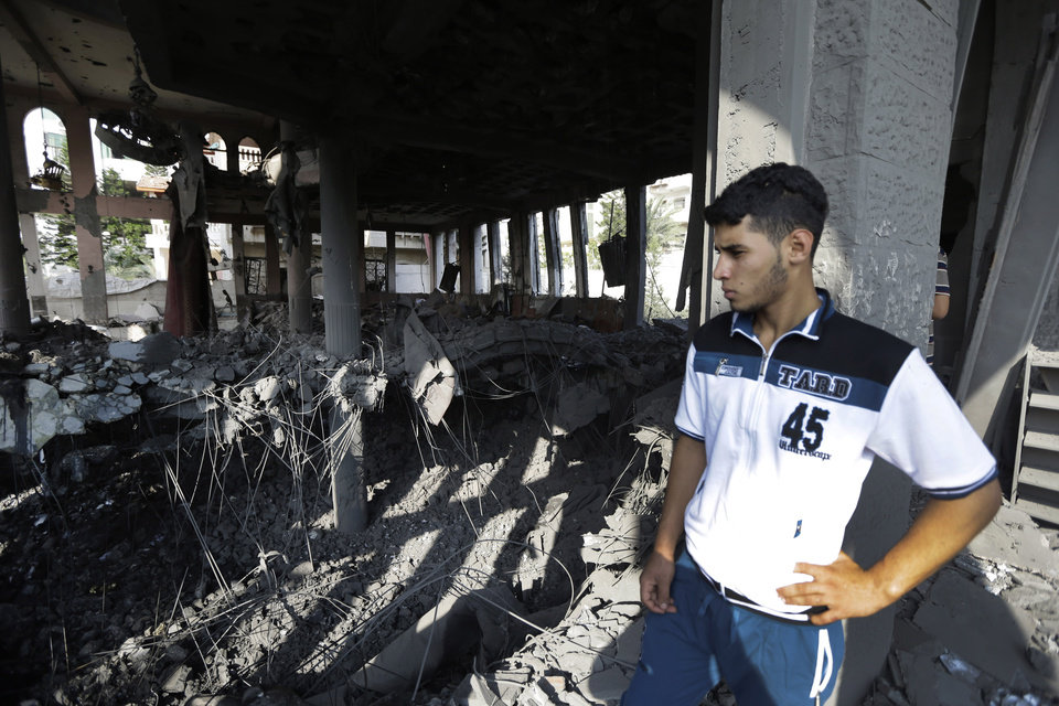 Photo - A Palestinian inspects the damage at the Ameen mosque in Gaza City, northern Gaza Strip, destroyed by an Israeli strike, Tuesday, July 29, 2014. Early Tuesday, Israel warplanes struck a series of targets in Gaza City, including the top Hamas leader in Gaza, Ismail Haniyeh's house and government offices, while Gaza's border area with Israel was hit by heavy tank shelling. (AP Photo/Lefteris Pitarakis)