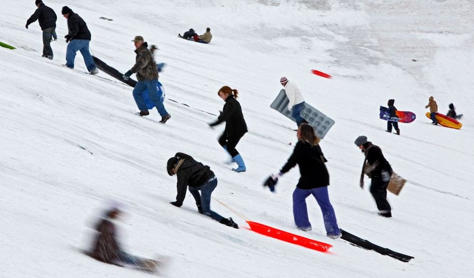 Photo -  A crowd of people make their way up a hill as people sled at Will Rogers Park in Oklahoma City, Saturday, Jan. 30, 2010.  Photo by Bryan Terry, The Oklahoman