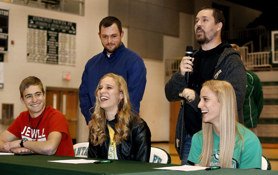 Photo - Athletes Emily Hart and her sister, Erin Hart, and Stephen Snider, far left,  laugh at comments made by their coach when introducing the Hart sisters to the audience before a group of Edmond Santa Fe seniors signed their letters. Erin and Emily Hart  signed letters to participate in track and field at Oklahoma Baptist University in Shawnee. Snider  signed a letter to participate in cross country and track and field at William Jewell College during signing day ceremony in the gymnasium at Edmond Santa Fe High School on Wednesday, Feb. 5, 2014.    Photo by Jim Beckel, The Oklahoman