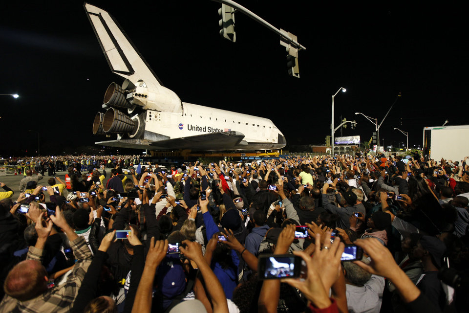 Spectators take pictures as the space shuttle Endeavour is pulled by a Toyota Tundra pickup truck on its way across the 405 freeway in Inglewood, Calif., Friday, Oct. 12, 2012. Endeavour's 12-mile road trip kicked off shortly before midnight Thursday as it moved from its Los Angeles International Airport hangar en route to the California Science Center. (AP Photo/Patrick T. Fallon)