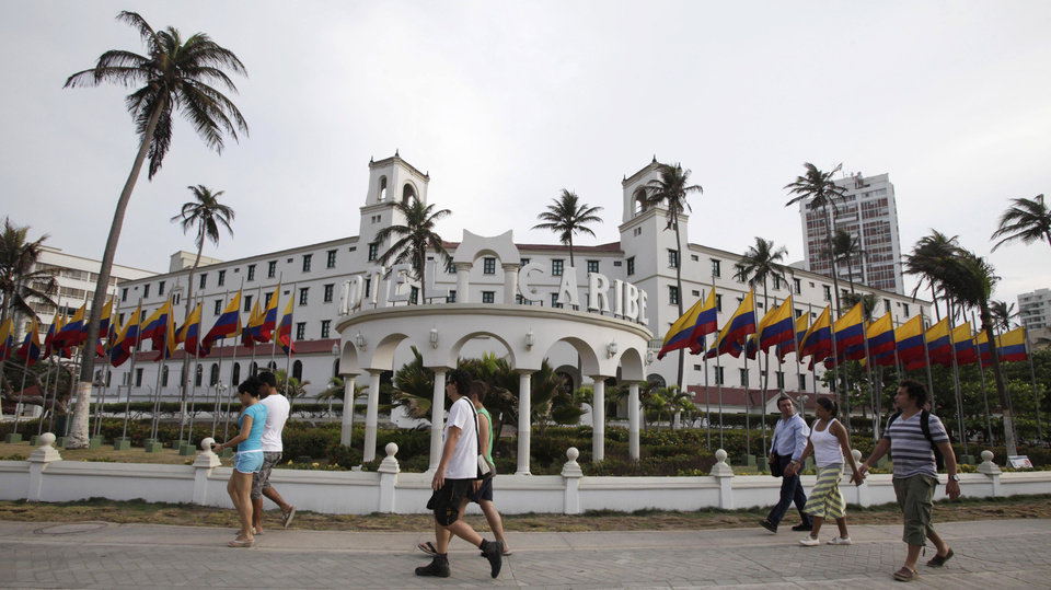 Photo -   People walk past Hotel El Caribe in Cartagena, Colombia, Saturday April 14, 2012. The Secret Service sent home some of its agents for misconduct that occurred at the hotel before President Barack Obama's arrival on Friday for the Summit of the Americas. (AP Photo/Fernando Vergara)