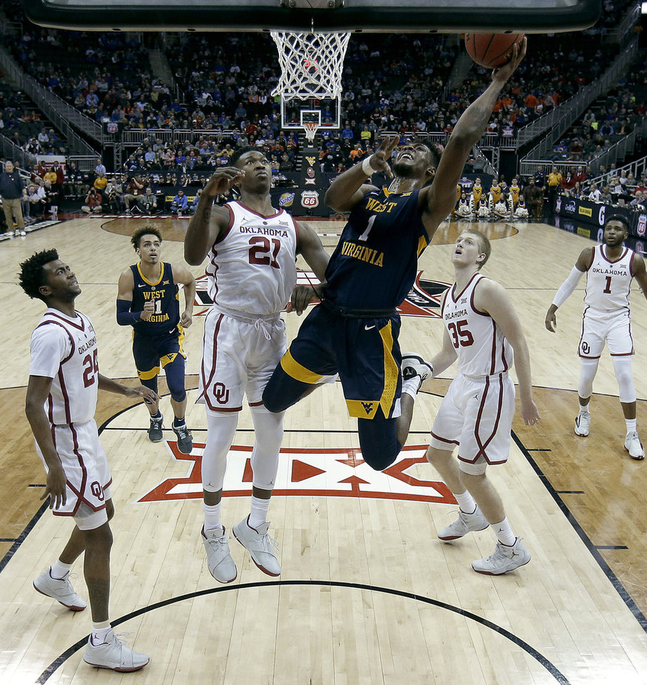 Photo - West Virginia's Derek Culver (1) gets past Oklahoma's Kristian Doolittle (21) to put up a shot during the first half of an NCAA college basketball game in the Big 12 men's tournament Wednesday, March 13, 2019, in Kansas City, Mo. (AP Photo/Charlie Riedel)
