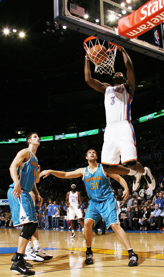 Photo - Oklahoma City's DJ White (3) dunks the ball in front of Jason Smith (14) and Aaron Gray (34) of New Orleans during the preseason NBA basketball game between the New Orleans Hornets and the Oklahoma City Thunder at the Ford Center in Oklahoma City, Thursday, October 21, 2010. The Thunder won, 101-86. Photo by Nate Billings, The Oklahoman