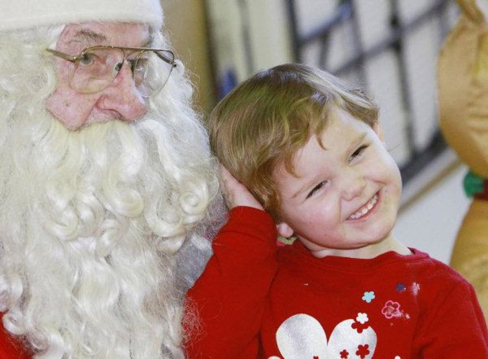 Nevaeh Hill, 3, strikes a pose for a photo with Santa. PHOTOS BY DAVID MCDANIEL, THE OKLAHOMAN