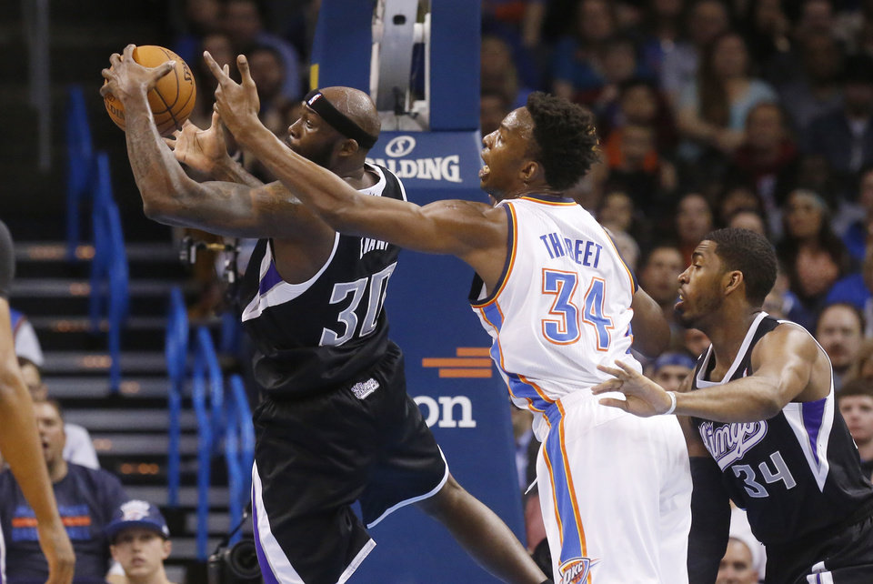 Photo - Sacramento Kings forward Reggie Evans (30) grabs a rebound in front of Oklahoma City Thunder center Hasheem Thabeet (34) and Sacramento's Jason Thompson (34) in the first quarter of an NBA basketball game in Oklahoma City, Friday, March 28, 2014. (AP Photo/Sue Ogrocki)