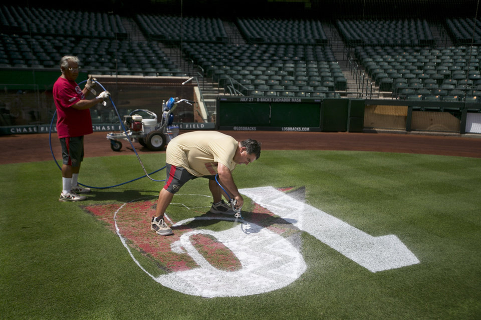 "Diamondbacks head groundskeeper Grant Trenbeath, right, paints a ""19"" logo behind home plate at Chase Field in Phoenix Thursday, July 4, 2013, honoring the fallen firefighters from the Yarnell Hill Fire.  Assistant groundskeeper Manny Lugo holds the paint hose. (AP Photo/The Arizona Republic, David Wallace)  MARICOPA COUNTY OUT; MAGS OUT; NO SALES"