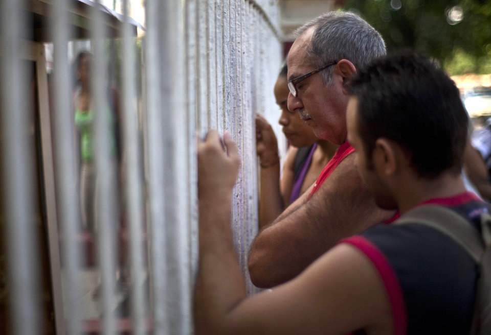 Photo -   People read adjustments to the migratory policy, posted on a wrought iron fence of an immigration office in Havana, Cuba, Tuesday, Oct. 16, 2012. The Cuban government announced Tuesday that it will no longer require islanders to apply for an exit visa, eliminating a much-loathed bureaucratic procedure that has been a major impediment for many seeking to travel overseas for more than a half-century. (AP Photo/Ramon Espinosa)