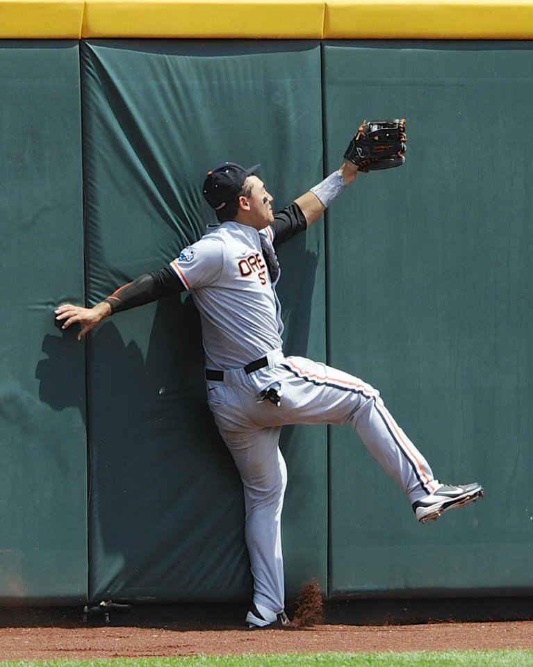 Photo - Oregon State left fielder Michael Conforto crashes into the wall as he catches a fly ball hit by Mississippi State's Wes Rea in the second inning of an NCAA College World Series baseball game in Omaha, Neb., Friday, June 21, 2013. (AP Photo/Eric Francis)