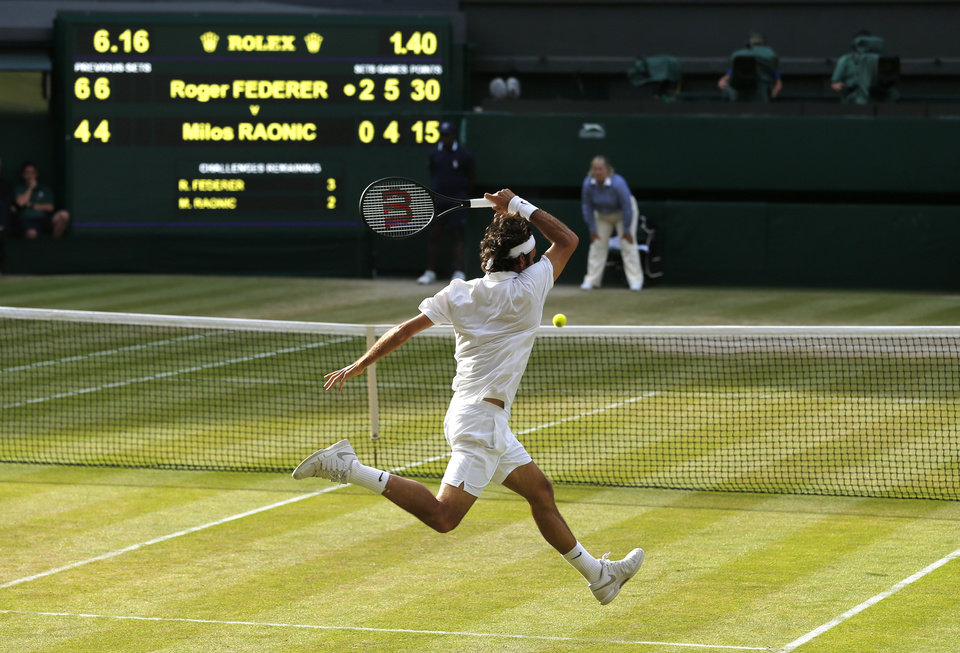 Photo - Roger Federer of Switzerland plays a return to go to match point in his game against Milos Raonic of Canada during their men's singles semifinal match at the All England Lawn Tennis Championships at Wimbledon, London, Friday, July, 4, 2014. (AP Photo/Ben Curtis)