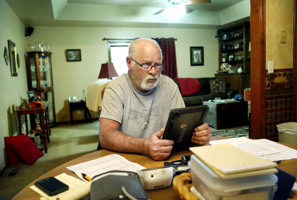 Photo -  Kurtis Kennedy, who was diagnosed with pancreatic cancer, talks to Andrew Clark, a physician assistant, using an electronic device while seated at the dining room table in his Edmond home. [Photo by Jim Beckel, The Oklahoman]