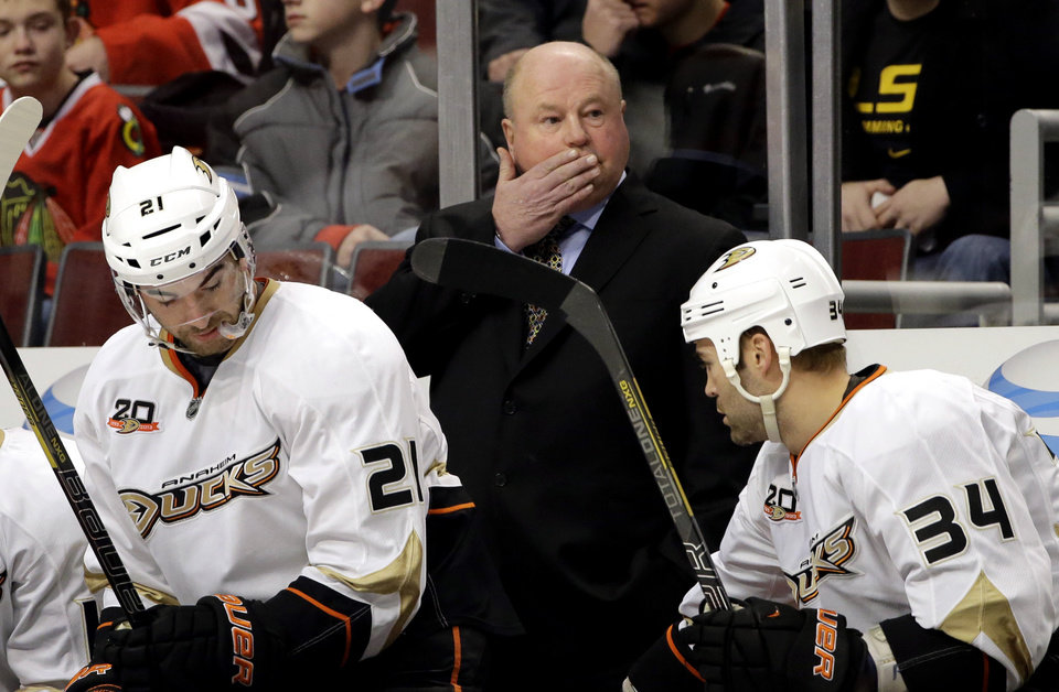 Photo - Anaheim Ducks coach Bruce Boudreau wipes his face as he watches his team during the first period of an NHL hockey game against the Chicago Blackhawks in Chicago, Friday, Jan. 17, 2014. (AP Photo/Nam Y. Huh)