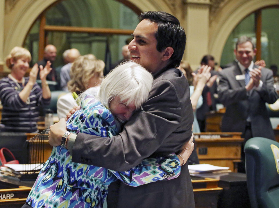 Rep. Diane Mitsch Bush, D-Steamboat Springs, and Rep. Dan Pabon, right, D-Denver, hug as the legislature closes its session in the House chambers on Wednesday, May 8, 2013. (AP Photo/Ed Andrieski)