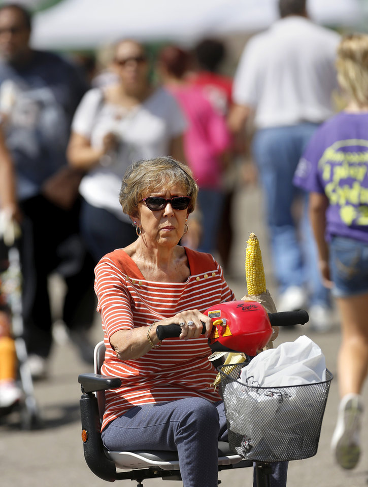 Photo - A woman steers an electric cart while holding an ear of roasted corn at the Oklahoma State Fair on Wednesday, , Sep. 18, 2013. Photo  by Jim Beckel, The Oklahoman.