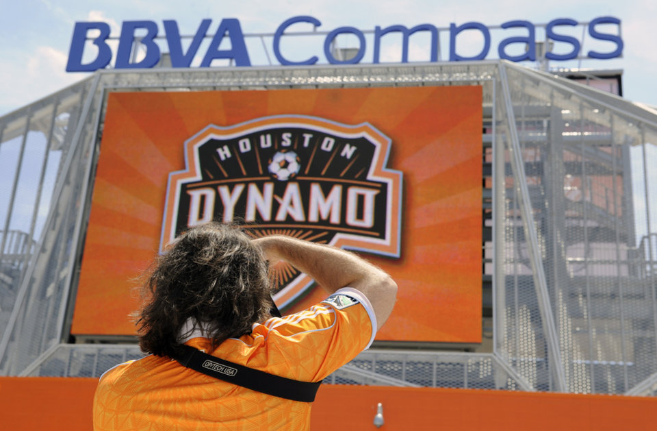 Photo -   A Houston Dynamo fan takes a picture of the new BBVA Compass stadium before the inaugural soccer game against D.C. United Saturday, May 12, 2012, in Houston. (AP Photo/Pat Sullivan)