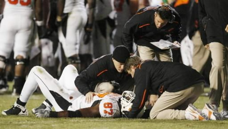 Photo - Head coach Mike Gundy, top, watches as OSU's Brandon  Pettigrew (87) is examined after being hurt in the second half during the college football game between Oklahoma State University and University of Colorado at Folsom Field in Boulder, Colo., Saturday, Nov. 15, 2008.  Pettigrew later came back into the game. OSU won, 30-17. BY NATE BILLINGS, THE OKLAHOMAN