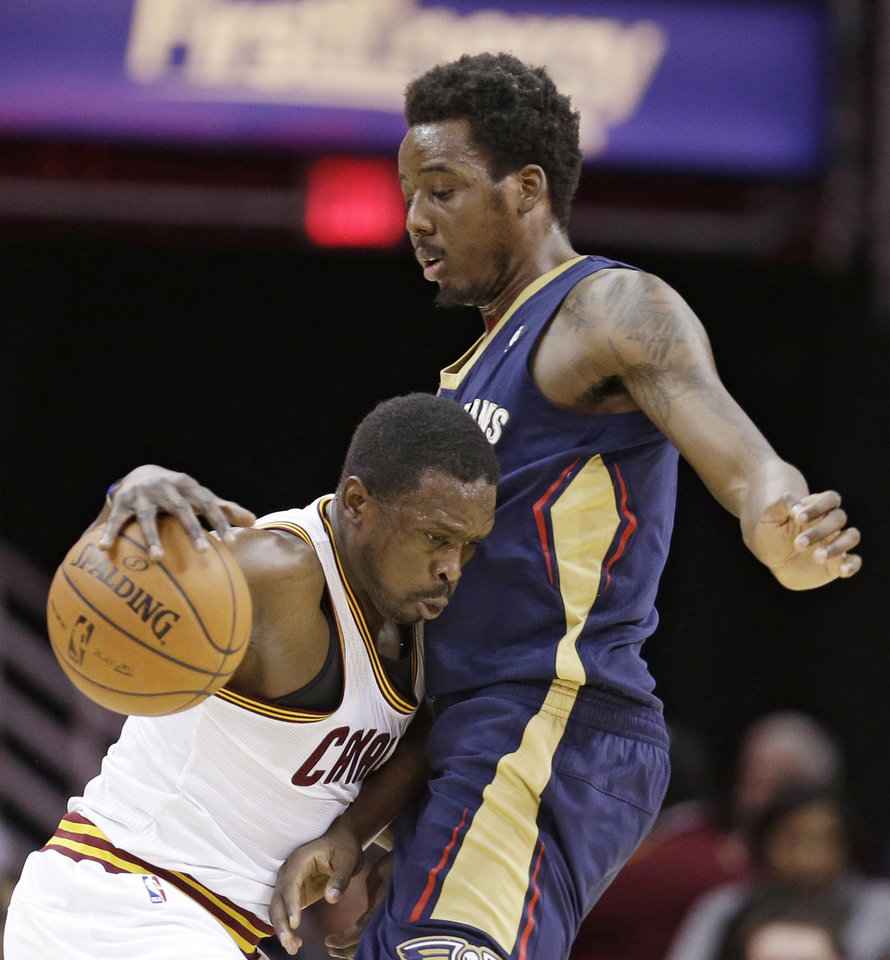 Photo - Cleveland Cavaliers' Luol Deng, left, from Sudan, drives around New Orleans Pelicans' Al-Farouq Aminu, right, during the first quarter of an NBA basketball game, Tuesday, Jan. 28, 2014, in Cleveland. (AP Photo/Tony Dejak)