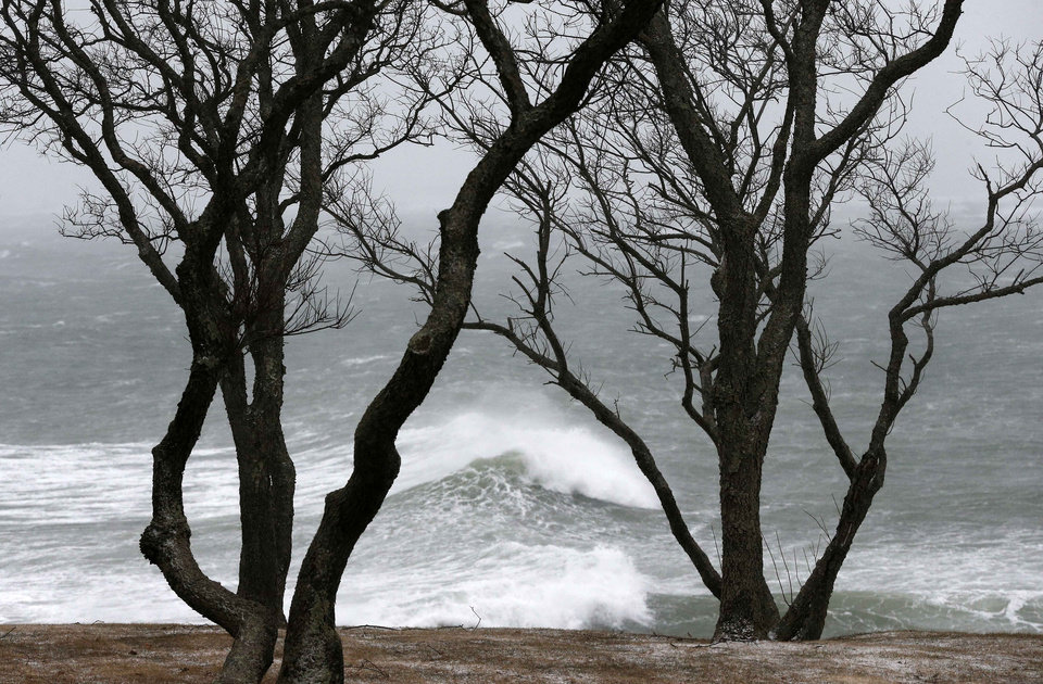 Photo - Wind-driven waves come ashore in Scituate, Mass., Wednesday, March 26, 2014. Cape Cod and the islands were expected to bear the brunt of the spring storm that struck full force Wednesday. The storm could drop up to 10 inches of snow with winds up to 70 miles per hour. (AP Photo/Michael Dwyer)