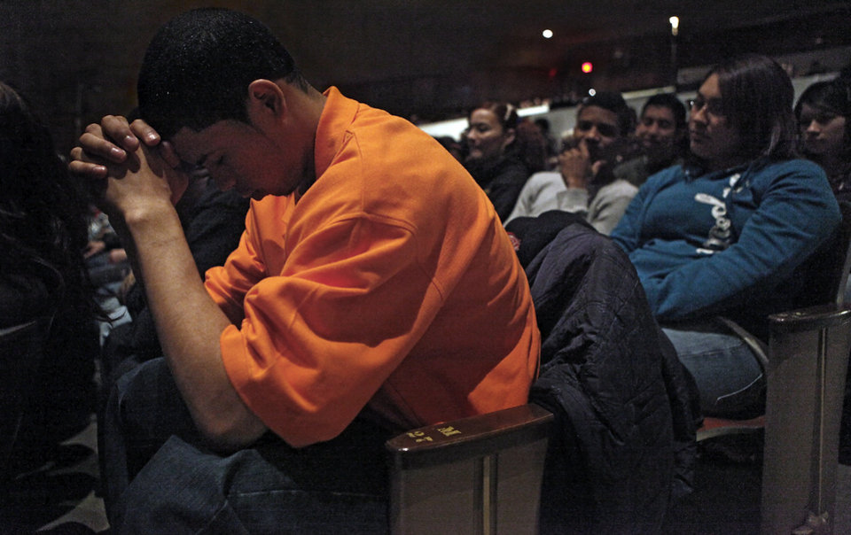 Photo - Northwest Classen senior Rico Navarro lowers his head in prayer as classmates gather in the school's auditorium on Tuesday, Jan. 20, 2009, in Oklahoma City to watch the inauguration of President Barack Obama in Washington D.C.  PHOTO BY CHRIS LANDSBERGER, THE OKLAHOMAN
