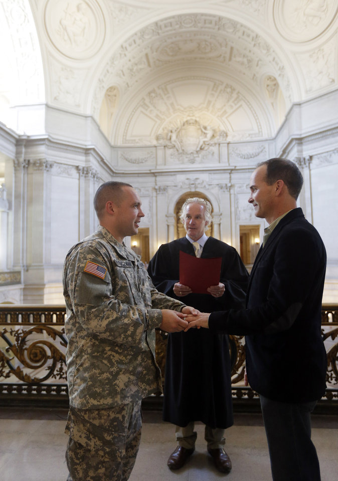 Photo - Army Capt. Michael Potoczniak,  at left, and Todd Saunders, right, of El Cerrito, Calif., exchange rings as they are married by deputy marriage commissioner John Loschmann, center, at City Hall in San Francisco, Saturday, June 29, 2013.  Dozens of gay couples waited excitedly Saturday outside of San Francisco's City Hall as clerks resumed issuing same-sex marriage licenses, one day after a federal appeals court cleared the way for the state of California to immediately lift a 4 ½ year freeze. Big crowds were expected from across the state as long lines had already stretched down the lobby shortly after 9 a.m. City officials decided to hold weekend hours and let couples tie the knot as San Francisco is also celebrating its annual Pride weekend expected to draw as many as 1 million people. (AP Photo/Marcio Jose Sanchez)