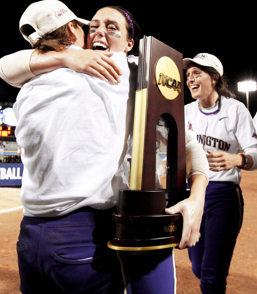 Photo - Washington's Danielle Lawrie, center, hugs teammate Aly McWherter in front of Amanda Fleischman after the Huskies' win over Florida in Game 2 of the WCWS championship series on Tuesday.  Photo by Bryan Terry, The Oklahoman