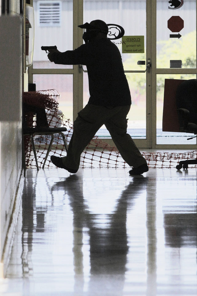 In this photo taken July 11, 2013, a Clarksville public schools faculty member, wearing a protective mask, participates in active-shooter training at the city\'s high school in Clarksville, Ark. Twenty Clarksville School District staff members are training to be armed security guards on campus. (AP Photo/Danny Johnston)