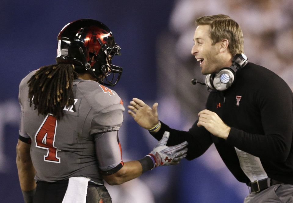 Texas tech coach Kliff Kingsbury congratulates wide receiver Bradley Marquez after his touchdown reception against Arizona State during the first half of the Holiday Bowl NCAA college  football game Monday, Dec. 30, 2013, in San Diego. (AP Photo/Gregory Bull)