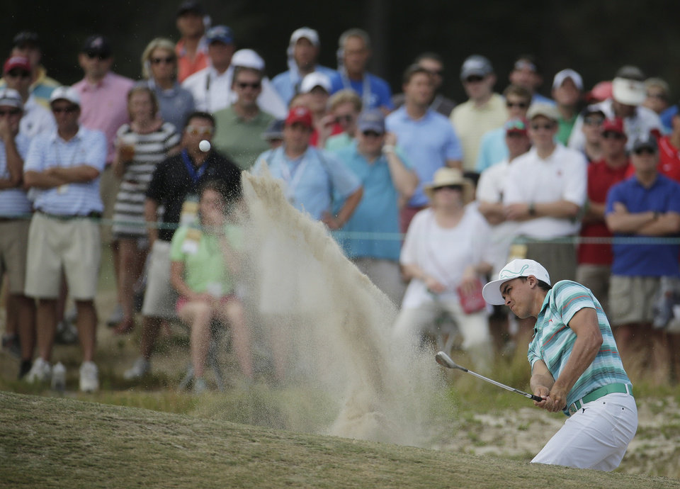 Photo - Rickie Fowler hits out of the bunker on the 11th hole during the third round of the U.S. Open golf tournament in Pinehurst, N.C., Saturday, June 14, 2014. (AP Photo/Charlie Riedel)