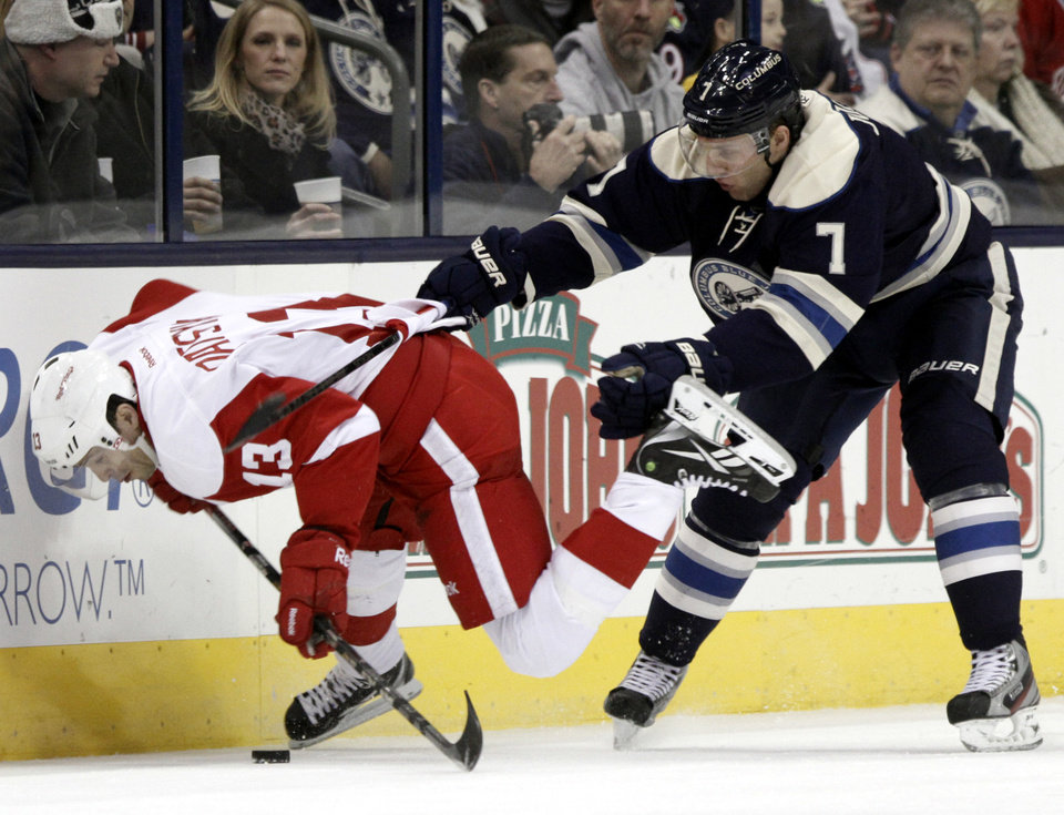 Photo - Columbus Blue Jackets' Jack Johnson, right, checks Detroit Red Wings' Pavel Datsyuk, of Russia, in the second period of an NHL hockey game in Columbus, Ohio, Saturday, Feb. 2, 2013. (AP Photo/Paul Vernon)