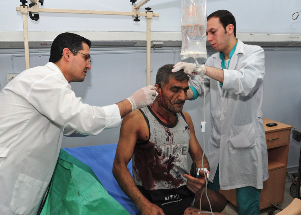 In this photo released by the Syrian official news agency SANA, Syrian doctors treat an injured man who was wounded after two bombs exploded, at Qazaz neighborhood in Damascus, Syria, on Thursday May 10, 2012. Two strong explosions ripped through the Syrian capital Thursday, killing or wounding dozens of people and leaving scenes of carnage in the streets in an assault against a center of government power. (AP Photo/SANA) ORG XMIT: BEI112