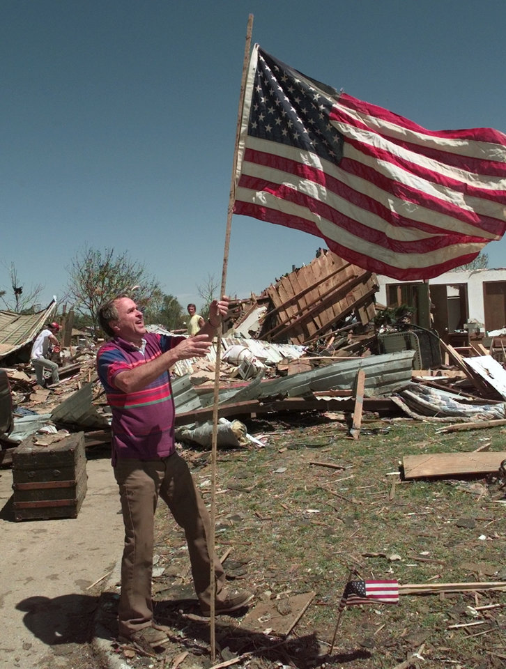 Tornado damage: Bob Douglas puts up an American flag at is daughter's home at 4725 SE 43rd. in Del City.
