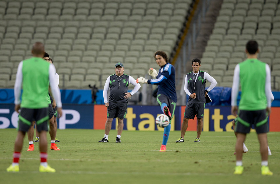 Photo - Mexico's coach Miguel Herrera, center back, observe his players during an official training session the day before the group A World Cup soccer match between Brazil and Mexico, at the Arena Castelao in Fortaleza, Brazil, Monday, June 16, 2014.  (AP Photo/Eduardo Verdugo)