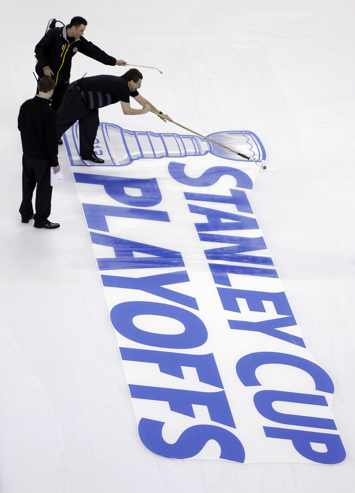 Photo - Workers attach a Stanley Cup Playoffs logo onto the ice at TD Garden in Boston, following an NHL hockey game between the Ottawa Senators and the Boston Bruins on Sunday, April 28, 2013. The Senators won 4-2. (AP Photo/Steven Senne)