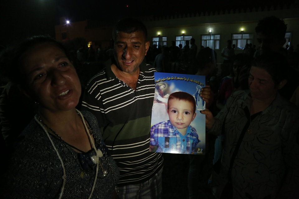 Photo - A displaced Iraqi Christian man, Adib Elias, holds a picture of his four-year-old son, David, who was killed by militants, at St. Joseph Church in Irbil, northern Iraq, Thursday, Aug. 7, 2014. Late Wednesday, militants overran a cluster of predominantly Christian villages alongside the country's semi-autonomous Kurdish region, sending tens of thousands of civilians and Kurdish fighters fleeing from the area, several priests in northern Iraq said Thursday. (AP Photo/Khalid Mohammed)