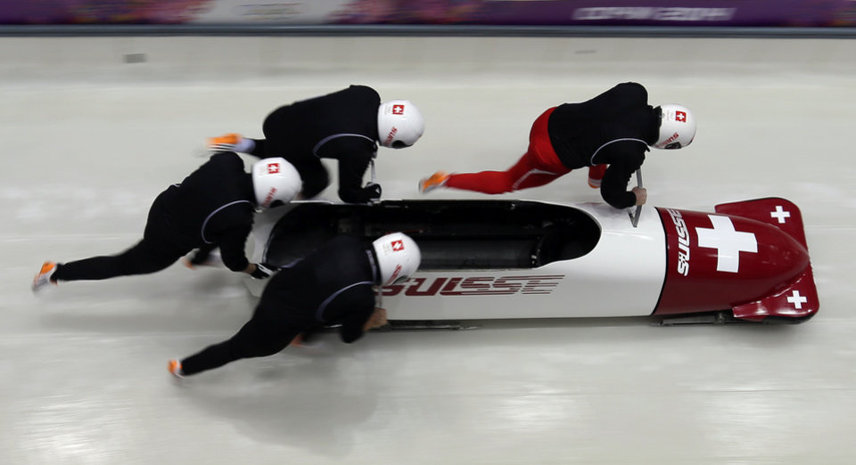 Photo - The team from Switzerland SUI-1, piloted by Beat Hefti, start a run during the men's four-man bobsled training at the 2014 Winter Olympics, Wednesday, Feb. 19, 2014, in Krasnaya Polyana, Russia. (AP Photo/Michael Sohn)