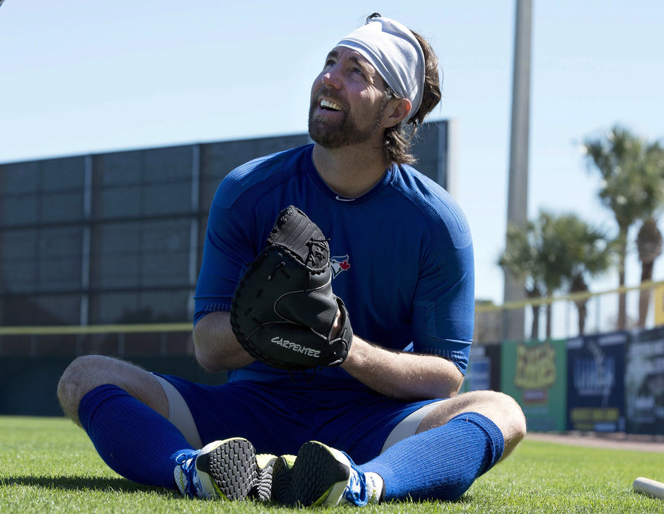 Photo - Toronto Blue Jays pitcher R.A. Dickey tries on a catcher's glove as he warms up at the stadium during spring baseball in Dunedin, Fla., on Sunday, Feb. 16, 2014. (AP Photo/The Canadian Press, Frank Gunn)