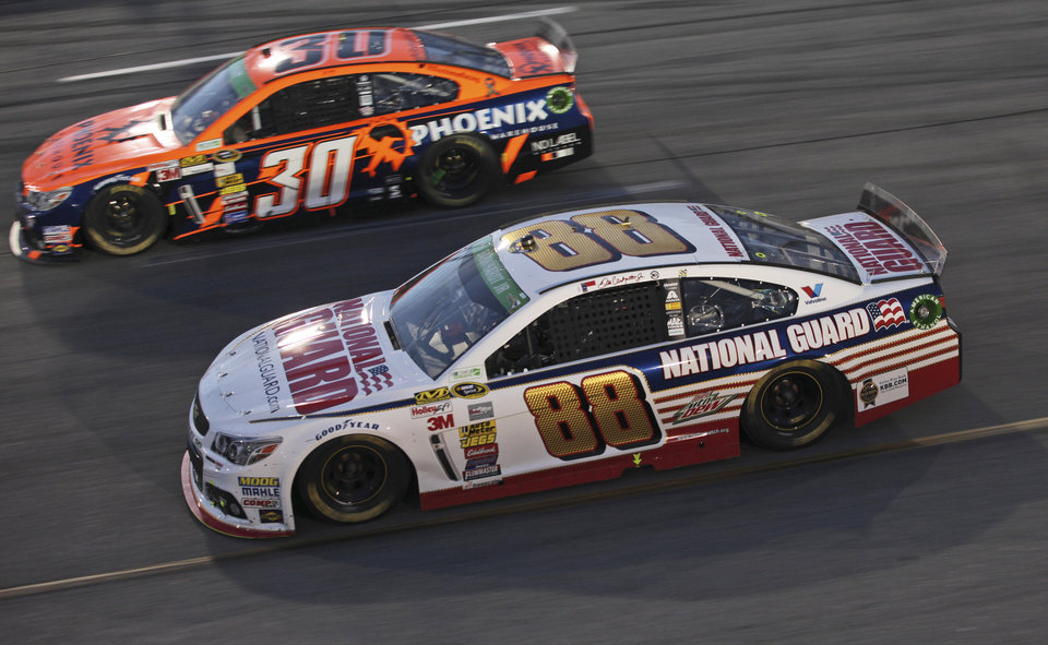 Photo - Dale Earnhardt Jr. (88) and JJ Yeley (30) race in Turn 4 during the NASCAR Sprint Cup auto race at Richmond International Raceway in Richmond, Va., Saturday, April 26, 2014. (AP Photo/Zach Gibson)