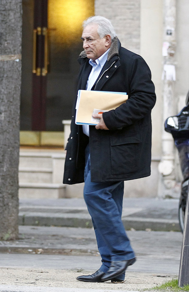 Former International Monetary Fund leader Dominique Strauss-Kahn leaves his apartment building in Paris, Monday Dec. 10, 2012. The outcome of a New York City hotel housekeeper's sexual assault lawsuit against  Dominique Strauss-Kahn will be settled Monday in a New York court.(AP Photo/Remy de la Mauviniere)