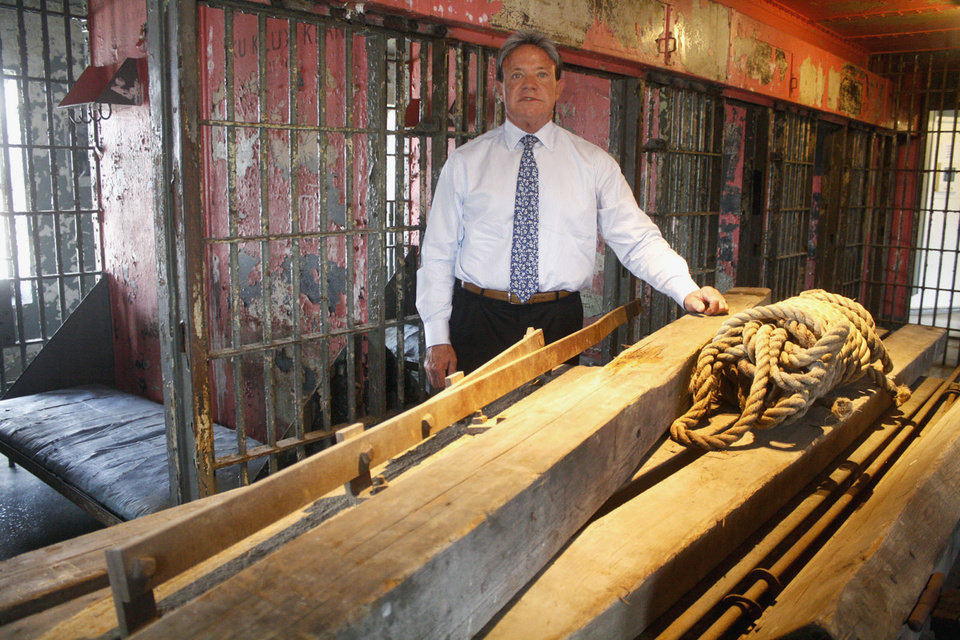 Photo - In this May 7, 2013 photo, Robert Rea, president of the Franklin County Historic Preservation Society, is pictured at the Franklin County Historic Jail Museum in Benton, Ill., with the wood and rebar pieces of the gallows that were used for the 1928 public hanging of notorious bootlegging gangster Charlie Birger in Benton. Birger was the last person to be publicly hanged in the state. Administrators at the museum got a call recently from a family that found the gallows in a barn in Grand Tower, Ill. The pieces were moved to the museum, which has had to make do for years with a replica of the gallows. The rope shown was used in the assembly of the gallows. (AP Photo/The Southern, Becky Malkovich)