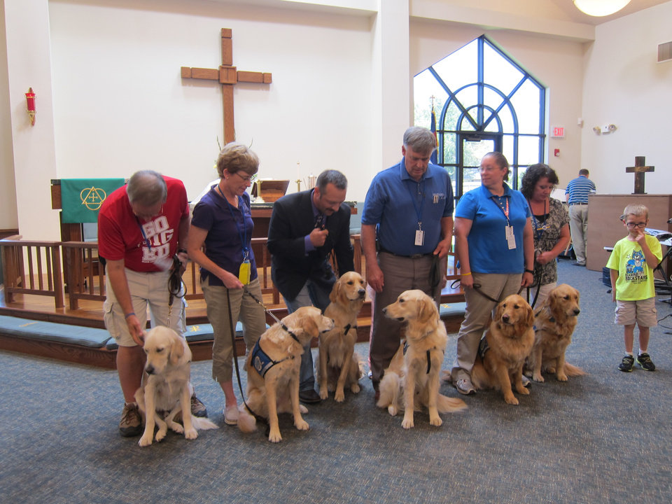 Photo -  All of the Lutheran Church Charities Comfort Dogs attending the recent Passing of the Leash ceremony for Rufus Comfort Dog prepare for a group picture with their handlers and helpers at St. Mark Lutheran Church in Edmond. Koey  Keylon, a member of St. Mark, and Rufus Comfort Dog are third from left. Photo by Carla Hinton, The Oklahoman