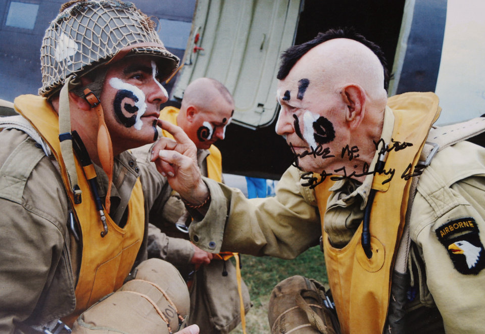 This photo shows McNiece, right, re-enacting the famous black and white photo taken by a Stars and Stripes photographer of him putting war paint on the face of a fellow paratrooper. This image was taken at an air show in Pennsylvania. Jake McNiece, 93, was a paratrooper with 101st Airborne who parachuted behind enemy lines in northern France and led a team of men dubbed the