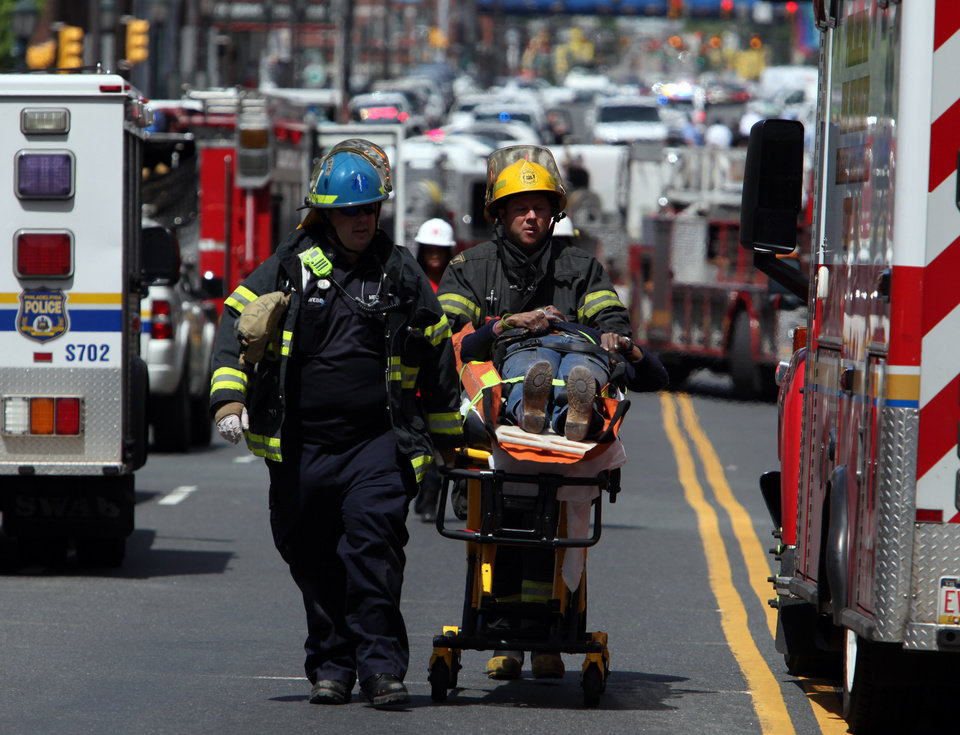 Photo - Rescue personnel evacuate an injured person from the scene of a building collapse in downtown Philadelphia Wednesday June 5, 2013.  A four-story building being demolished collapsed Wednesday on the edge of downtown, injuring 12 people and trapping two others, the fire commissioner said.  (AP Photo/Jacqueline Larma)