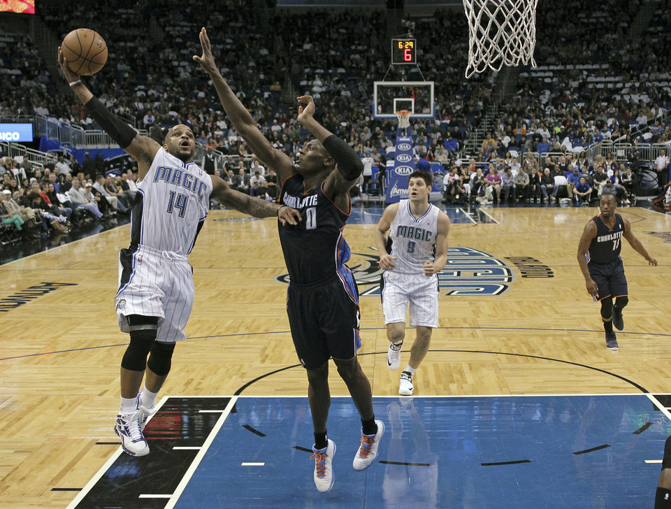Orlando Magic's Jameer Nelson (14) gets off a shot over Charlotte Bobcats' Bismack Biyombo (0) during the first half of an NBA basketball game, Friday, Jan. 18, 2013, in Orlando, Fla. (AP Photo/John Raoux)