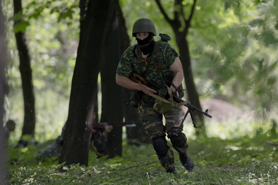 Photo - Pro-Russian gunmen take positions near the airport, outside Donetsk, Ukraine, on Monday, May 26, 2014. Ukraine's military launched air strikes Monday against separatists who had taken over the airport in the eastern capital of Donetsk in what appeared to be the most visible operation of the Ukrainian troops since they started a crackdown on insurgents last month. (AP Photo/Vadim Ghirda)
