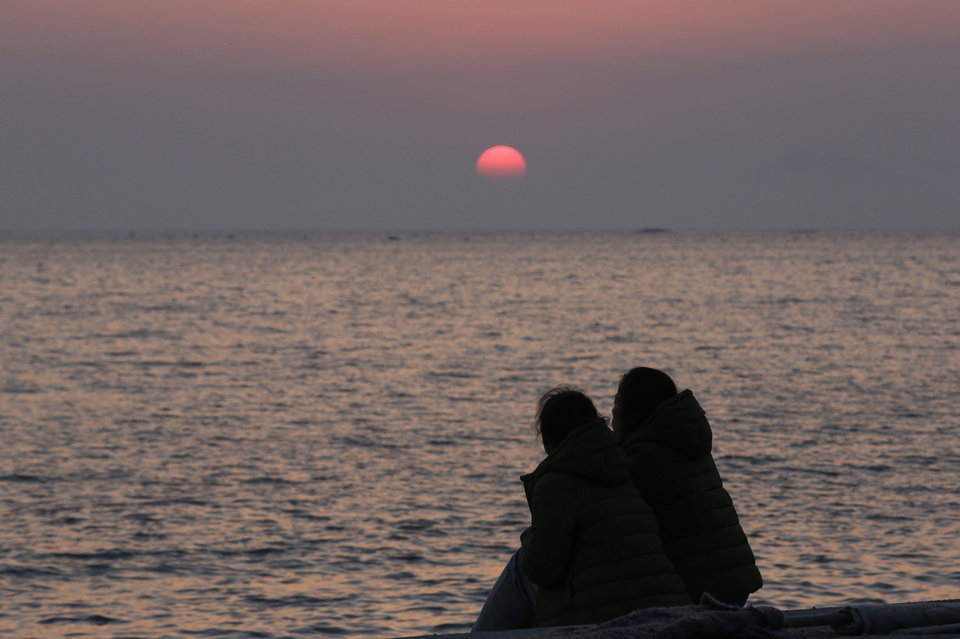 Photo - Relatives of passengers aboard the sunken ferry Sewol look towards the sea as they await news on their missing loved ones at sunset at a port in Jindo, south of Seoul, South Korea, Tuesday, April 22, 2014. One by one, coast guard officers carried the newly arrived bodies covered in white sheets from a boat to a tent on the dock of this island, the first step in identifying a sharply rising number of corpses from a South Korean ferry that sank nearly a week ago. (AP Photo/Lee Jin-man)