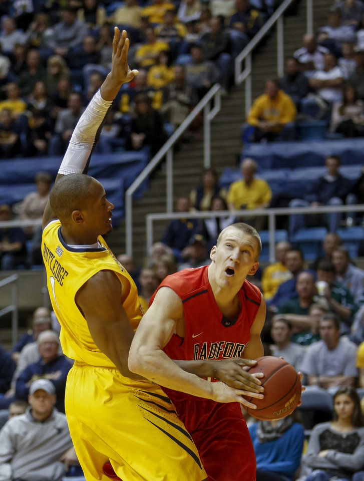 Radford's Lucas Dyer, right, is fouled by West Virginia's Dominique Rutledge, left, during the first half of an NCAA college basketball game at WVU Coliseum in Morgantown, W.Va., on Saturday, Dec. 22, 2012. (AP Photo/David Smith)