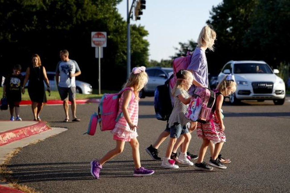 Photo -  Children are dropped off Friday at Chisholm Elementary School on their first day of school in Edmond. [Bryan Terry/The Oklahoman]