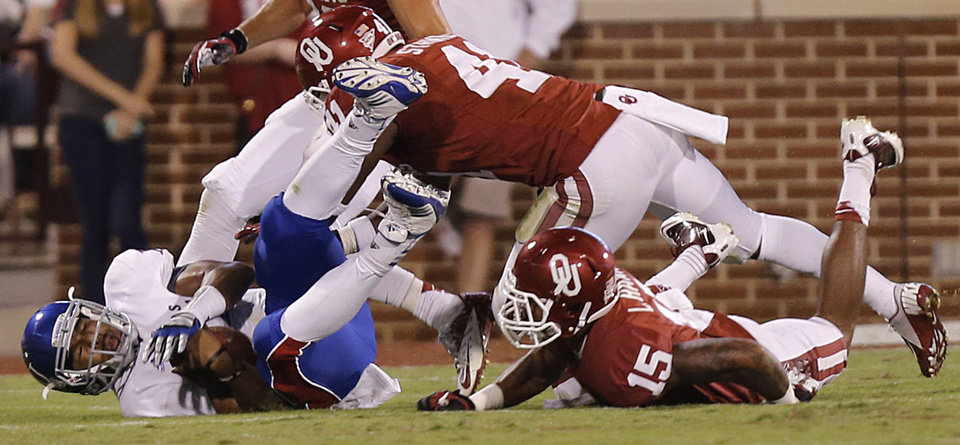 Photo - OU's Lamar Harris (15) and Eric Striker (41) bring down KU's Michael Cummings (14) during the college football game between the University of Oklahoma Sooners (OU) and the University of Kansas Jayhawks (KU) at Gaylord Family-Oklahoma Memorial Stadium on Saturday, Oct. 20th, 2012, in Norman, Okla. Photo by Chris Landsberger, The Oklahoman