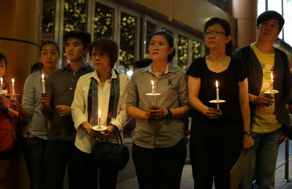 Photo - People hold candles during a ceremony in memory of passengers on board the missing Malaysia Airlines Flight MH370 in Kuala Lumpur, Malaysia, on Thursday, March 27, 2014. Australian officials say search operations for the missing Malaysia Airlines plane have been suspended for the day due to bad weather.  The flags are on half-staff to show solidarity and empathy with the family members of the passengers and crew of flight MH370. (AP Photo/Aaron Favila)