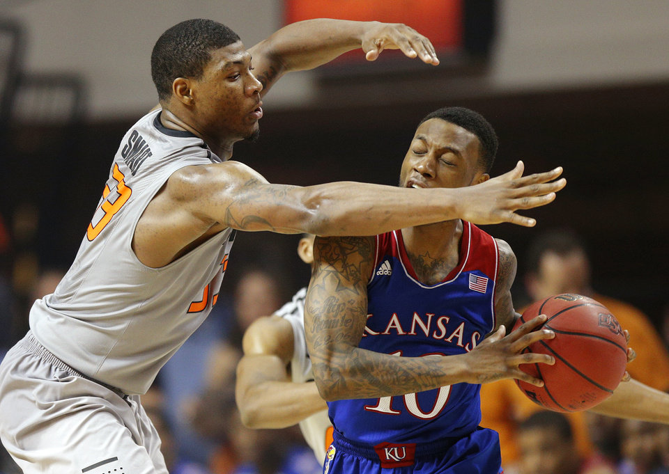 Photo - Oklahoma State's Marcus Smart (33) defends Kansas' Naadir Tharpe (10) during an NCAA college basketball game between Oklahoma State University (OSU) and the University of Kansas at Gallagher-Iba Arena in Stillwater, Okla., Saturday, March 1, 2014. Oklahoma State won 72-65. Photo by Bryan Terry, The Oklahoman